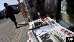 Phụ nữ Trung Quốc đi ngang qua một sạp báo Bắc Kinh, nơi trang nhất của một tờ báo đăng hình ảnh của Phó Chủ tịch Trung Quốc Tập Cận Bình gặp Tổng thống Hoa Kỳ arack Obama, ngày 16 tháng 2, 2012