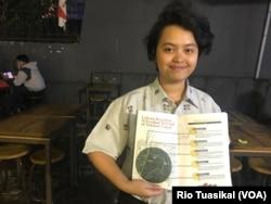 Redaktur Pelaksana Media Parahyangan Ranessa Nainggolan menunjukan majalah yang lembaganya terbitkan dan memuat sejumlah kasus pelecehan seksual di dalam dan sekitar Universitas Katolik Parahyangan (Unpar). (Foto Rio Tuasikal/VOA)