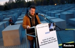 A volunteer of Berlin's Jewish community reads out all names of Jews killed in the city during the Holocaust at the Holocaust Memorial on the eve of the 80th anniversary of Kristallnacht, also known as Night of Broken Glass, a state-sponsored spree of looting and destruction of Jewish property across Germany and Austria in Berlin, Nov. 8, 2018.