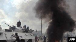 Xe của lực lượng duy trì hòa bình chạy ngang qua đoàn người ủng hộ ông Alassane Ouattara đang biểu tình