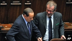 Italy's Prime Minister Silvio Berlusconi (L) talks with Interior Minister Roberto Maroni in Rome, October 14, 2011.