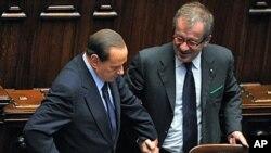 Italy's Prime Minister Silvio Berlusconi (L) talks with Interior Minister Roberto Maroni in Rome, October 14, 2011.
