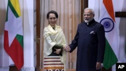 FILE - Myanmar State Counsellor Aung San Suu Kyi, left, and Indian Prime Minister Narendra Modi pose for the media ahead of their meeting in New Delhi, India, Jan. 24, 2018.