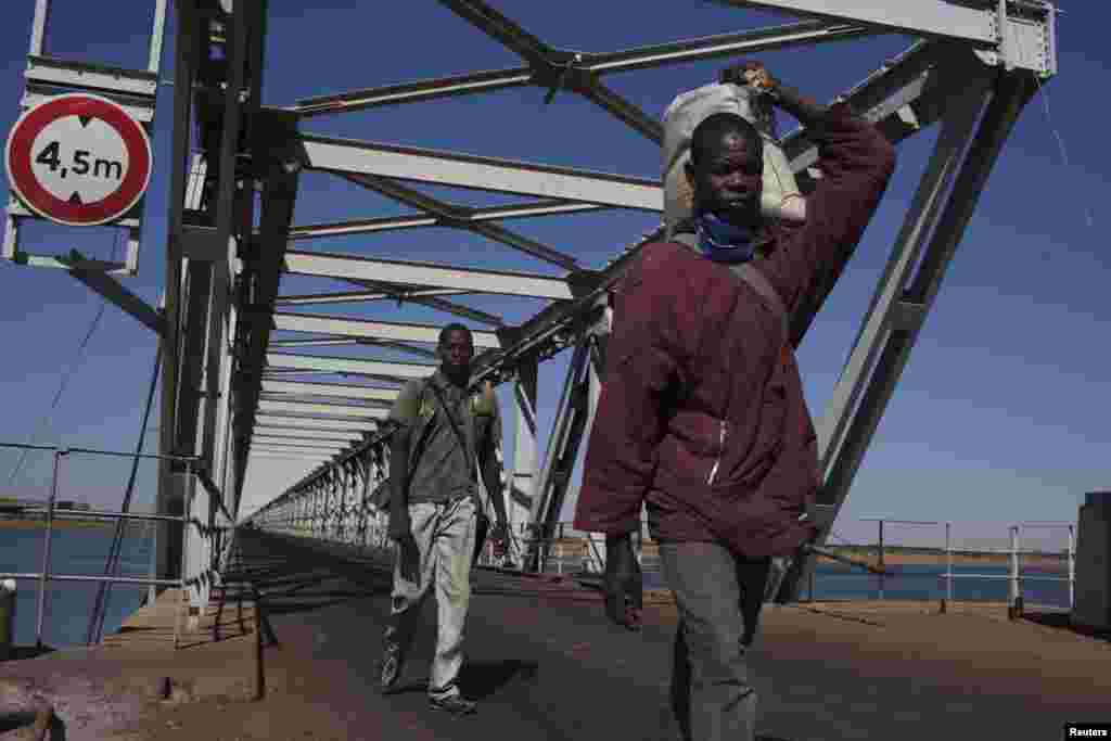 People cross a strategic bridge over a dam on the Niger River secured by French forces in Markala, Mali, January 18, 2013.