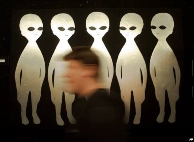 A patron passes a painting inside the International UFO Museum and Research Center in Roswell, N.M., Tuesday, June 10, 1997. The small town is bracing for its biggest invasion yet, the 50th anniverary of an alleged UFO crash. (AP Photo/Eric Draper)