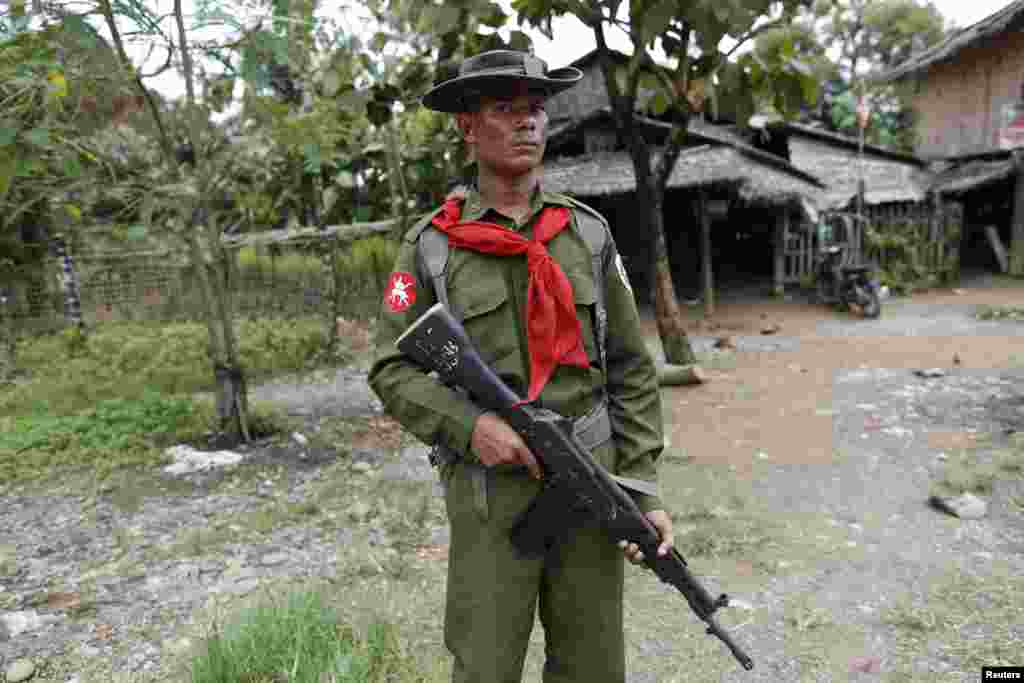 A soldier stands guard near Muslim homes at Shwe Lay village, outside of Thandwe in the Rakhine state, western Burma, Oct. 2, 2013.