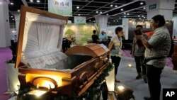 Visitors look at a paper casket at the Asia Funeral and Cemetery Expo & Conference in Hong Kong, May 18, 2017. Asia's aging population is projected to hit 923 million by midcentury, according to an Asian Development Bank, putting the region on track to be