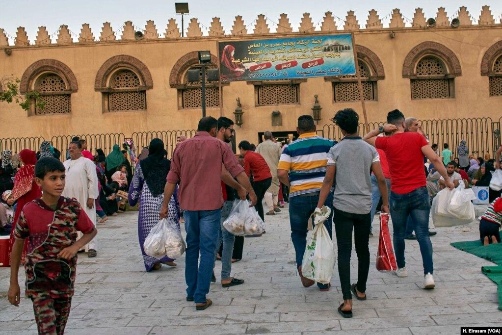 Мусульмане прибывают до заката в мечеть с едой и напитками, чтобы прервать свой пост в Старом Каире, Египет, 31 мая 2019 года.