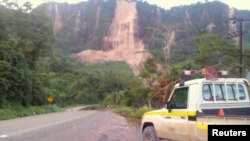 Warga setempat memeriksa lokasi tanah longsor dan jalan yang rusak dekat Kota Tabubil setelah gempa kuat yang mengguncang Dataran Tinggi Selatan di Papua Nugini, 26 Februari 2018. F(Foto: Jerome Kay via Reuters)