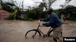 Một người đàn ông đẩy xe đạp qua khu vực ngập nước sau khi cơn bão Matthew đi qua Haiti, ngày 4 tháng 10 năm 2016.