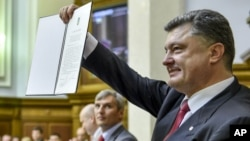 Ukrainian President Petro Poroshenko shows the Ukraine-EU Association Agreement to lawmakers after its signing it in parliament in Kiev, Ukraine Tuesday, Sept. 16, 2014. Ukraine's parliament ratified an agreement to deepen economic and political ties with the European Union on Tuesday, and passed legislation to grant autonomy to the rebellious east as part of a peace deal. (AP Photo/Mykola Lazarenko)