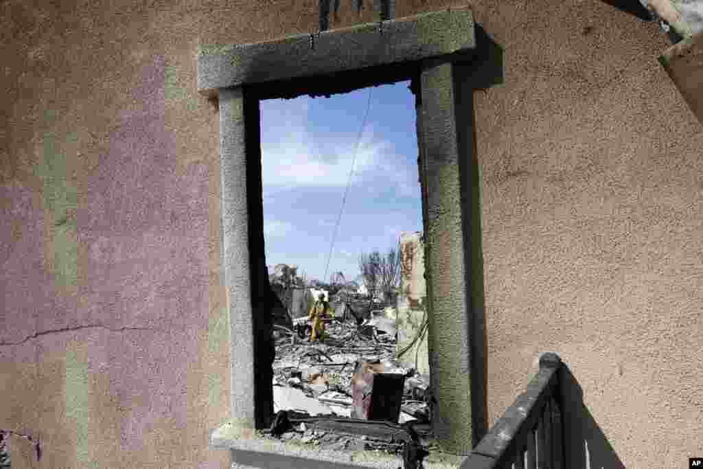 Un bombero revisa una vivienda quemada en Carlsbad, California.