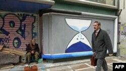 Čistač cipela sedi ispred zatvorene radnje ispisane grafitima u centru Atine, 12. mart, 2012.