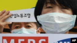 FILE - Members of Korea Health and Medical Workers' Union stage a rally to protest against the Samsung Medical Center's lack of control in preventing the spread of MERS (Middle East Respiratory Syndrome) in front of the center in Seoul, South Korea, June 19, 2015.