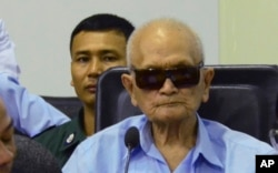 In this photo released by the Extraordinary Chambers in the Courts of Cambodia, Nuon Chea, center, who was the Khmer Rouge's chief ideologist and No. 2 leader, sits in the court room during a hearing at the U.N.-backed war crimes tribunal, in Phnom Penh,