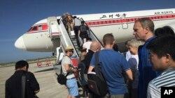 Para penumpang menaiki tangga pesawat Air Koryo yang akan berangkat menuju Beijing, di Bandara Internasional Pyongyang, Korea Utara, 27 Juni 2015. (Foto: dok).