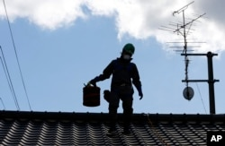 FILE - A worker wearing cleans radiation-exposed roof tiles at a private house in Minamisoma, Fukushima prefecture, northeastern Japan, Feb. 24, 2016. About 7,000 day laborers are cleaning up this irradiated town north of the Fukushima nuclear plant.