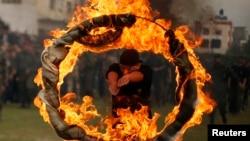 Seorang warga Palestina melompat ke dalam lingkaran api sebagai tanda kelulusan sebuah pendidikan ala militer di Gaza, 14/1/2014.