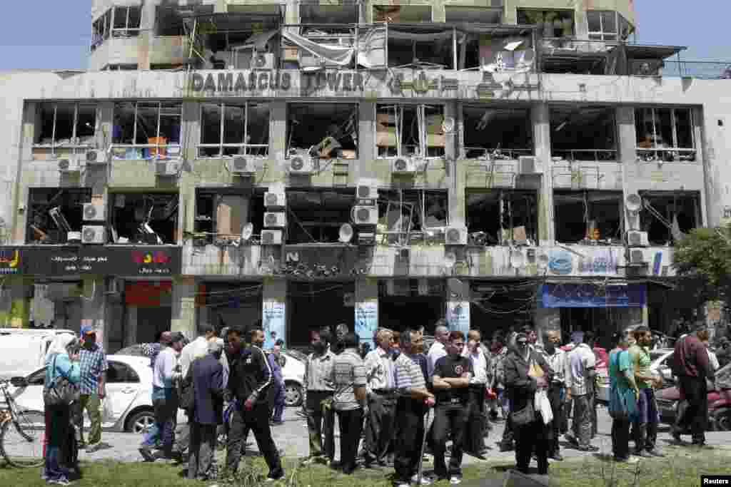People stand on a street lined with a damaged building and destroyed cars after a blast at Marjeh Square in Damascus, April 30, 2013.