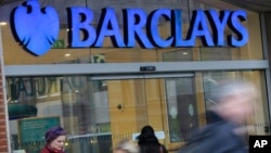 Customers wait outside a retail branch of Barclays Bank to open in London in this February 12, 2013, file photo.