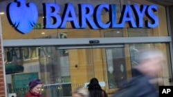 Customers wait outside a retail branch of Barclays Bank for the bank to open in London.