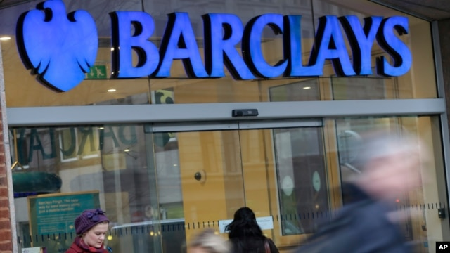 Customers wait outside a retail branch of Barclays Bank for the bank to open in London, Feb. 12, 2013.