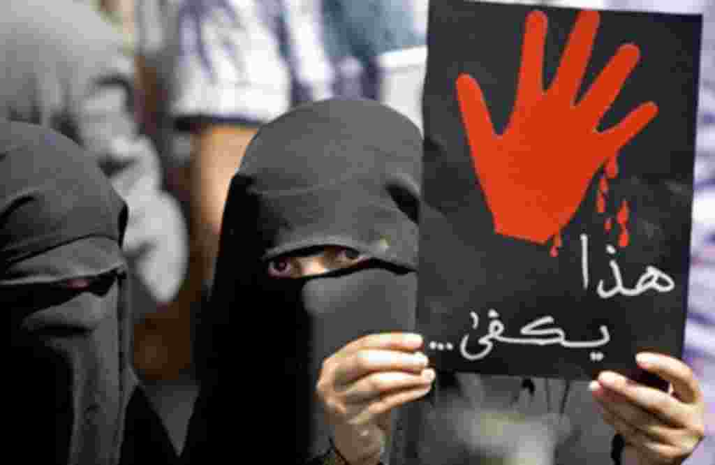 A Yemeni anti-government protester holds up a placard that reads 'This is enough' during an anti-regime demonstration calling on President Ali Abdullah Saleh to leave in the capital Sana'a, February 24, 2011