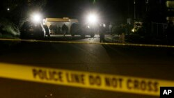 FILE - Crime-scene tape is shown as investigators work under lights at the scene of an overnight shooting.