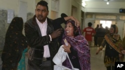 A man helps a woman injured in the suicide attack on a church, at a hospital in Quetta, Pakistan, Sunday, Dec. 17, 2017.