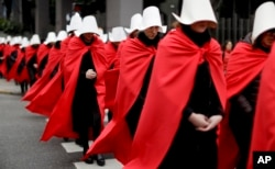 "FILE - Women in favor of a measure to expand legal abortions, wearing red cloaks and white bonnets like the characters from the novel-turned-TV series ""The Handmaid's Tale"", march in silence to Congress, in Buenos Aires, Argentina, July 25, 2018."