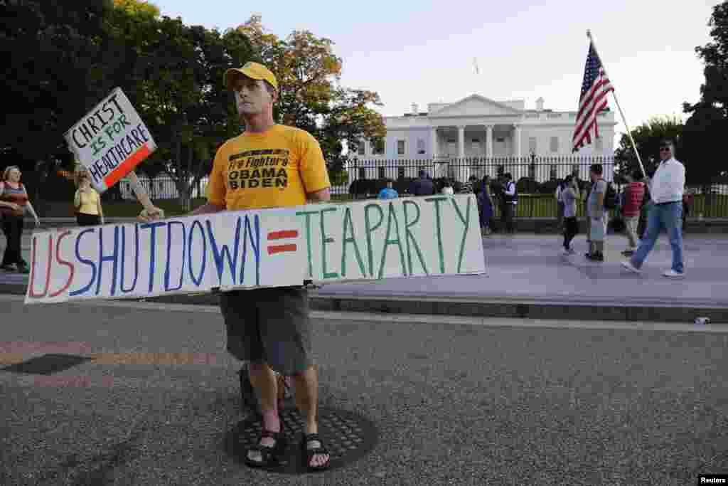Nhân viên cứu hỏa đã nghỉ hưu Eric Lamar cầm biểu ngữ ủng hộ chính quyền Obama trong cuộc biểu tình trước Tòa Bạch Ốc, ngày 4/10/2013.