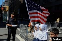 Anak-anak membawa bendera Amerika melewati petugas kepolisian New York dalam pawai tahunan Hari Muslim di New York, 24 September 2017. (Foto: REUTERS/Stephanie Keith)