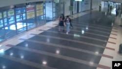 """華盛頓都會區機場管理局公布的照片顯示12歲的馬金晶(譯音)2018年8月2日與一名女子走過機場的""""行李/抵達""""樓層"""