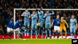 Les joueurs de Manchester City , y compris Yaya Touré , au centre, sautent pour bloquer un tir de de Kevin Mirallas d'Everton, deuxième à gauche, lors du match de football de la première league anglaise entre Manchester City et Everton au stade Etihad, Manchester, en Angleterre , le samedi 6 décembre 2014. (AP photo / Jon Super)