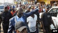 George Weah, candidat à la présidentielle libérienne de la Coalition pour le changement démocratique, au centre, salue la foule en plein Monrovia le 6 décembre 2017. / AFP PHOTO / Hugh Kinsella Cunningham