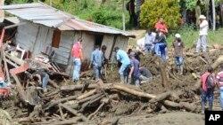 Residentes en Salgar tratan de salvar algunas de sus pertenencias después de la avalancha de lodo que sepultó sus viviendas.