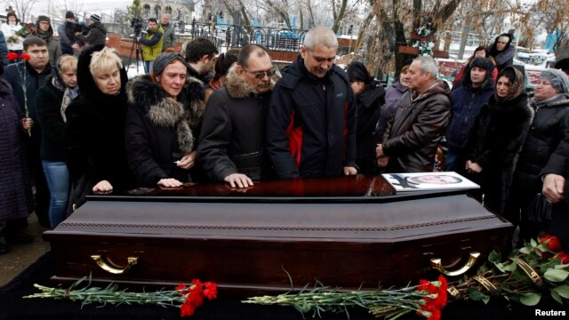 Relatives gather around the coffin of a victim of an explosion at a funeral in Volgograd, Dec. 31, 2013.