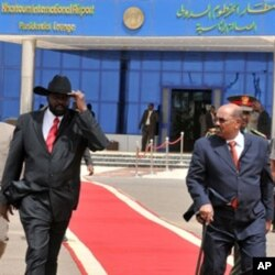 Sudanese President Omar al-Beshir (R) walks with Sudan's First Vice President and south Sudan leader Salva Kiir at the airport in Khartoum, as he prepares to leave for Chad, 21 Jul 2010