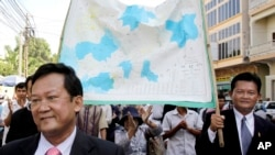 FILE - Marchers with opposition Sam Rainsy Party hold a Cambodia map supporting territorial claims against Vietnam on a street in Phnom Penh.