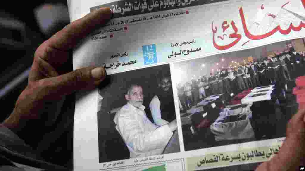 An Egyptian holds Al-Ahram newspaper with a picture of the arrested leader of the Muslim Brotherhood, Cairo, August 20, 2013.