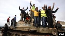 """Para demonstran anti-pemerintah mengacungkan tanda kemenangan (""""V"""" atau victory) dengan berdiri di atas sebuah tank militer di kota Benghazi (24/2)."""