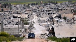 지난 4월 시리아 코바니 지역에서 자동차 한 대가 쿠르드족 민병대와 ISIL간 충돌로 폐허가 된 마을을 지나고 있다. (자료사진)