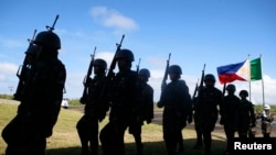 FILE - Soldiers march at Guiuan airport to take part in the welcoming ceremony for visiting French President Francois Hollande in Guiuan, Samar, a town that was devastated by Typhoon Haiyan in central Philippines, February 27, 2015.