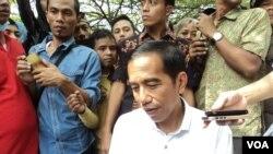 Capres Jokowi dikawal petugas berseragam batik saat berkunjung ke Pasar Barang bekas, Notoharjo, Solo, akhir pekan lalu. (VOA/Yudha Satriawan)
