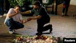 Seorang pria menghibur Joseph Culver (kiri) dari Charlottesville saat ia berdoa untuk temannya yang terluka ketika sebua mobil menabrak demonstran yang tidak mendukung gerakan ekstrem kanan dalam aksi protes di Charlottesville, Virginia, 13 Agustus 2017.