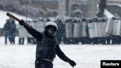 A pro-European protester gestures, with riot police officers seen in the background, during a rally in Kyiv, Jan. 22, 2014.