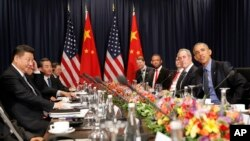 U.S. President Barack Obama, right, and China's President Xi Jingping, left, sit with members of their delegations for a meeting during the Asia-Pacific Economic Cooperation in Lima, Peru, Nov. 19, 2016.