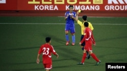 "A player from the Philippines receives a yellow card while playing against North Korea. Researchers are studying what makes a soccer official ""elite."""