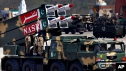 FILE - A missile is loaded on a vehicle during the Pakistan National Day parade in Islamabad, Pakistan, in March 2015. Pakistan's nuclear arsenal is on track to be the third largest in the world, one U.S. lawmaker said Wednesday.