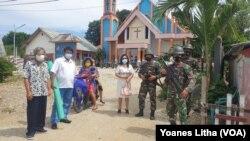 Jemaat berpose dengan tiga personel TNI dari Batalyon 714/ Sintuwu Maroso yang melakukan pengamanan di Gereja GKST Jemaat Elim Maliwuko. Jumat (25/12/2020). (Foto: VOA/Yoanes Litha)